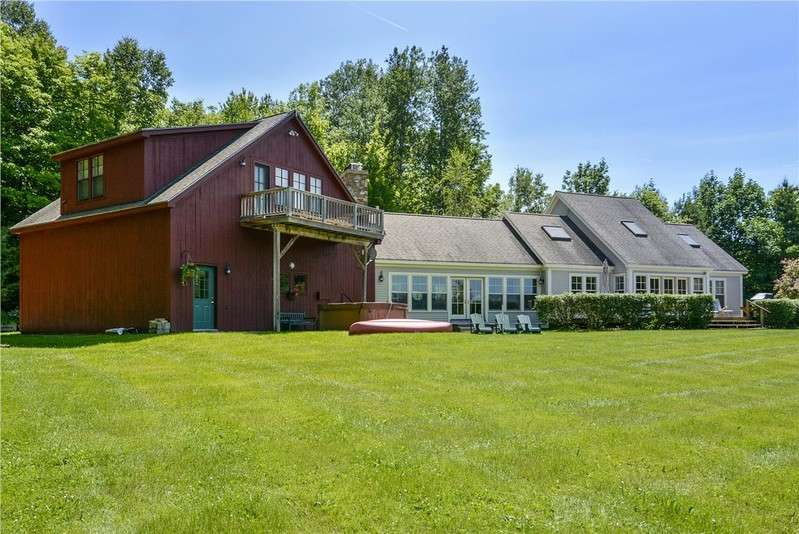 This gorgeous property features a swimming pond with a sandy beach in summer and panoramic views of the Trapp Family Lodge and Mount Mansfield in all seasons. The attached two car garage allows for complete comfort in winter and a master wing offers luxurious privacy and its own second story deck. The interior has been newly remodeled and designed with cherry floors, walls of windows and a floor to ceiling stone fireplace. The two story house is lavishly comfortable with a dynamite kitchen and true Butler's Pantry for entertaining in multiple social and dining areas. Clearly one of the most functional and beautiful kitchens in Stowe, this one is a knock-out and designed with multiple polished granite counters, farmhouse sink, butler's pantry, wine fridge, two dishwashers, breakfast bar and a range faucet on a six burner Viking gas range with gas and electric ovens. The grand living room with cathedral ceiling and wood burning stone fireplace has wraparound couches and a second dining area with expansive mountain views. Oversized couches and chairs invite you to stop for a moment and stay for the weekend! Staircases at both ends of the house lead to separate wings, one with two bedrooms that share a large bath and sleep five, and the other that leads to the private master wing with king sized bed, dressing room and spacious bathroom.