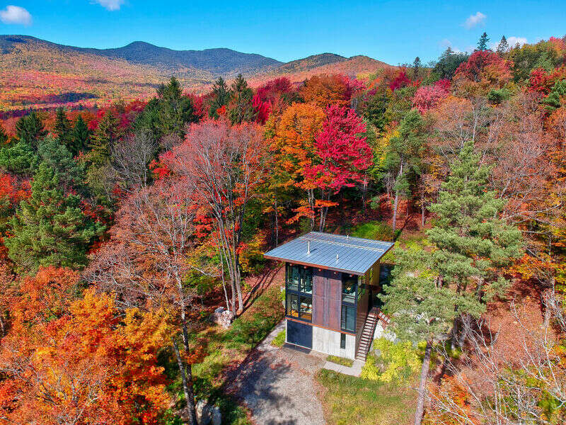 This modern yet cozy custom built cabin was designed for a couple who wanted a retreat to share their love of Vermont and the outdoors with their city kids. The end result is the Sterling Treehouse, a stunning modern cabin that integrates perfectly with the beauty ofthe Green Mountain State. The property is sited on 40+ acres overlooking Sterling Valley and has been designed to bring the outside in while masterfully interacting with its native surroundings. A soothing enclave of maple, raw steel, bronze, concrete and glass.  Theintention of the cabin isto be a retreat designed to bring families together to enjoy the majesty of the area.Thecabin has two large bedrooms with king beds and floor to ceiling windows, a bunk room that sleeps 5, agreat room with a table to seat 10, large screen TV, a Bang and Olufsen music system, and the deepest bathtub you'll ever find. The home is primarily furnished with hand crafted American made furniture and has bike storage, ski racks, and boot warmers to encourage families to get outside. To start or end the day, enjoy a two level patio with aStahl fire pit and insert for wood-fired grillingand spectacular views of the surrounding forest and Green Mountain ridge lines. Adjacent to the property are hiking, cross country skiing, and mountain biking trails, a 19th century cemetery, and old stone walls and foundations from the long gone Sterling settlement.Within walking distance from the house is the Sterling Gorge (an amazing place to hike, ice climb, or just enjoy the waterfalls), the VAST trail, the Catamount Trail, and the Sterling Forest mountain bike trails. The house is a 15 minute drive from the village of Stowe and 25 minutes from the Mountain Resort- take the back roads and skip the mountain traffic!Aaron Leitz Photography