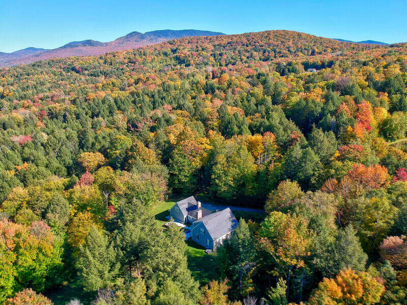 """Two Chimneys exudes classic Vermont styling in a scenic, private setting to match.Spacious enough to host a large group while still maintaining a cozy feel, this 5 bedroom 4.5 bath home has recently been renovated, with air conditioning added to all bedrooms in August 2019.Three of the five bedrooms are king bed master suites with en suite bathrooms for privacy.Access to the fifth bedroom is located through the attached garage. This cape-style house has two wood burning fireplaces for cold weather coziness and provides multiple living/entertainment areas.Year-round access to the large deck leads to views overlooking manicured lawns in the summer and ski slopes in the winter.Steps away are a gas grill and a new 7 person hot tub with water features and mood lighting.The kitchen includes updated amenities with a dedicated wine fridge and a massive quartz top island that is a perfect gathering place for the group.Just off the kitchen, the dining room comfortably seats 12.The two car garage allows for weather-proof access to the house and storage of outdoor gear. For entertainment, there are new 55"""" HD and 43"""" HD televisions, each with Blu-ray disc players and DISH satellite TV access.A pool table and ping pong table complement the offerings of this gorgeous vacation home.Located on a mountainside just south of the Stowe Village, you are steps away from the village and mountain and all the year-round activities that the Stowe area offers."""