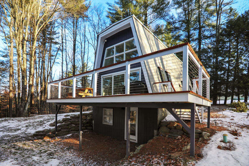 A cozy light filled A -frame cabin nestled in the woods and in the heart of Stowe's Lower Village. Thisnewly renovated three bedroom, two bathroom propertyhas been modernized with brand new appliances, colorful rugs and a spiral staircase leading up to a private bedroom.A second bedroom is on the main floor with a nearby bathroom, while the third bedroom is on the lower level.The wrap around deck has a gas grill for barbecues for a small group.This makes a perfect getaway for anyone wanting the quintessential Vermont experience. The lower level's open floor plan lets everyone enjoy the vacation together while the private bedrooms makeyou feel right at home. Large windows let in the light and give you a peek at Stowe's scenery, entreating you to head outside and experience it in person.For winter sports enthusiasts, the closest Mountain Road shuttle stop is only 0.3miles from the door. HOUSE IS CERTIFIED WITH FIRE DETECTORS, CARBON MONOXIDE DETECTORS AND FIRE EXTINGUISHERS. (Please note that this property has only spiral staircases that are narrow and steep. Guests with pets, young children, or those with mobility concerns may find a better match among our other rentals.)
