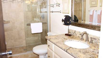 The hall bath has granite countertops, tile floors & a large tiled shower.
