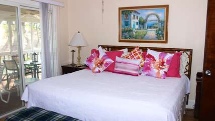 The master bedroom has a king bed and great golf course view through the live oaks.