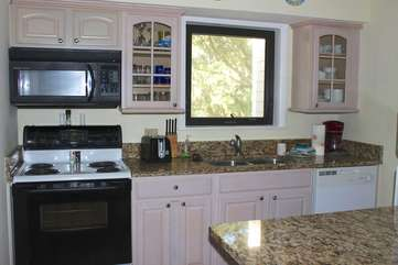 The updated kitchen has granite counters and updated cabinetry.