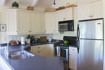 The kitchen has wainscoting, white cabinets and stainless steel appliances.