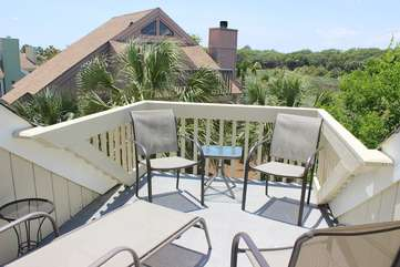 Sliding doors lead to the upper deck. Sun while resting on the chaise and chairs.