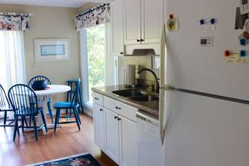 The eat-in kitchen has stone counters and hardwood floors.