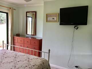 A mounted TV is in the 2nd bedroom.