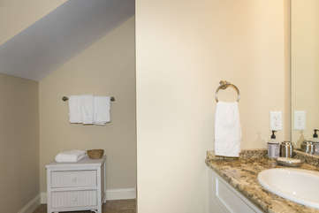 There is a full bath next to this bedroom. It has a large tile shower and a granite vanity .