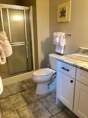 The bathroom has a large vanity, new tile flooring and a shower.