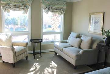 There is a sitting area with ocean views and doors leading to the deck.