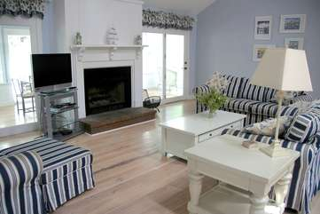 The great room has high ceilings, a fireplace and opens ot a sun room.