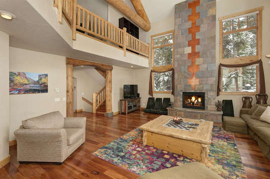Living room with fireplace, vaulted ceilings, picture windows