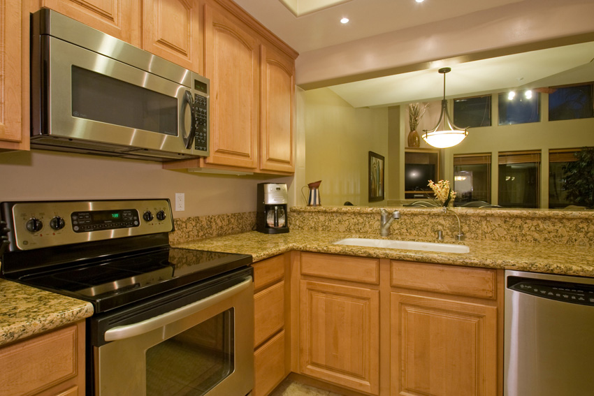Kitchen has stainless steele appliances and slab granite counters