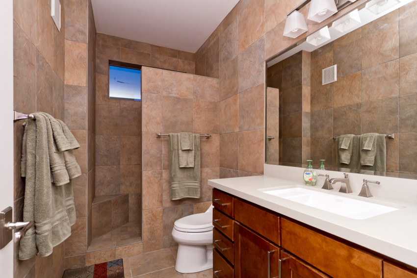 This guest bath is equipped with a nice walk-in shower with a built-in bench