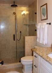 This luxurious bath has a tiled shower w/ a river rock floor & rain shower head.