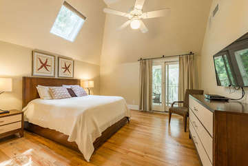 Upstairs, the 2nd bedroom has a queen bed and mounted HDTV.  French doors open to a balcony to relax on after a day at the beach.