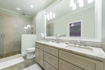 The extra large tiled shower feature a rain head and a glass surround in this totally renovated bathroom.