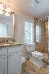 he bath has a granite topped vanity and stone flooring with walk in shower.