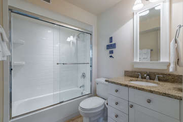 The adjoining bath has a tiled shower/tub, stone floor, and granite vanity.