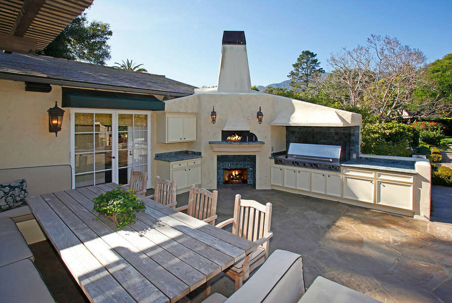 Outdoor kitchen with fireplace and pizza oven