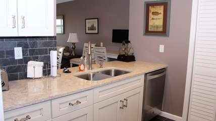 The kitchen has been expanded and features custom counters and granite counters.