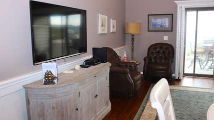 The living room has hardwood floors and sliding doors leading to a deck.