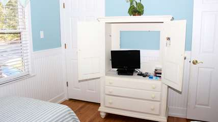 The cabinet has an flat screen TV and space for your clothing.