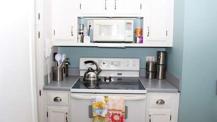 The kitchen has tile flooring and white cabinets and Corian counters.