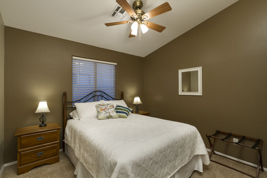 guest bedroom has a queen bed, ceiling fan, two nightstands with lamps.