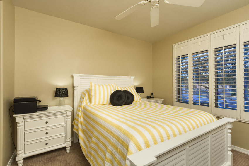 Guest bedroom #3 with two bedside tables and lamps and a ceiling fan.