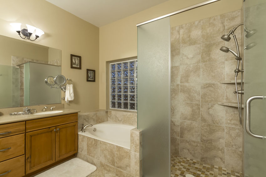 Master bathroom shower is tile and glass and features two shower heads.