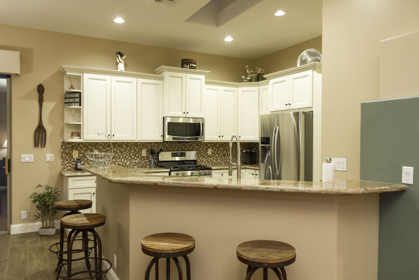 Kitchen with breakfast bar and four bar stools.