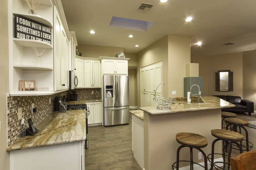 Kitchen has a skylight, solid granite counters, breakfast bar and a french door refrigerator with a water and ice dispenser.
