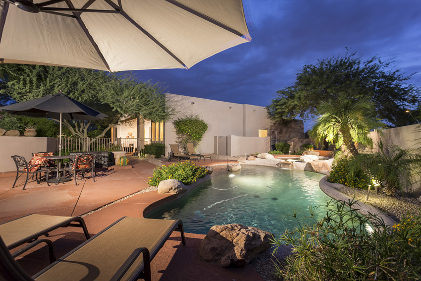 The pool area has four chaise lounge chairs and a table with four chairs. There are three umbrellas for added shade in the pool area.