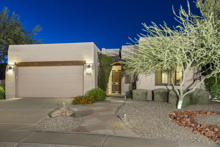 Front of home with 2 car garage and desert landscaping