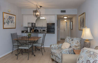 A cozy dining table is open to the living area and kitchen.