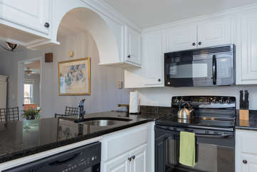 The renovated kitchen has new cabinetry and an arch opening.