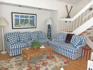Enjoy the open living area. This bright home has hardwood floors and an inviting blue and yellow decor.