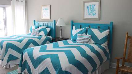 The 2nd bedroom has two full beds. Lively bright aqua/whites are featured.
