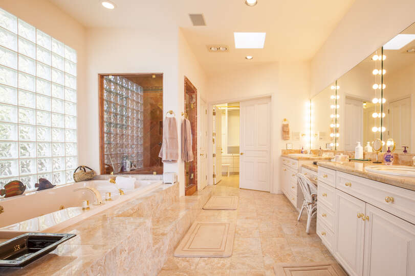 Lavish master bath has a double sink and vanity chair for the ultimate pampering experience