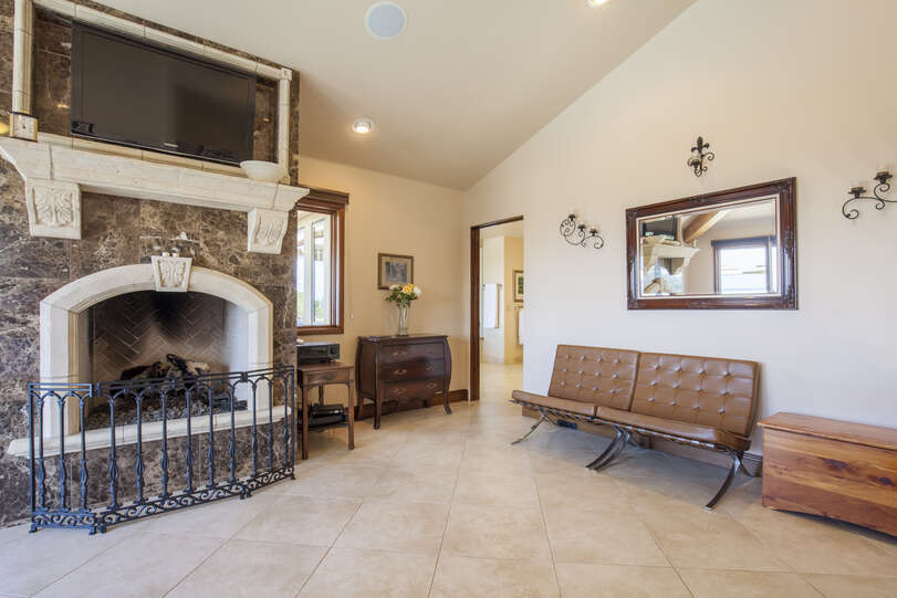 Detailed fireplace and large TV with seating area