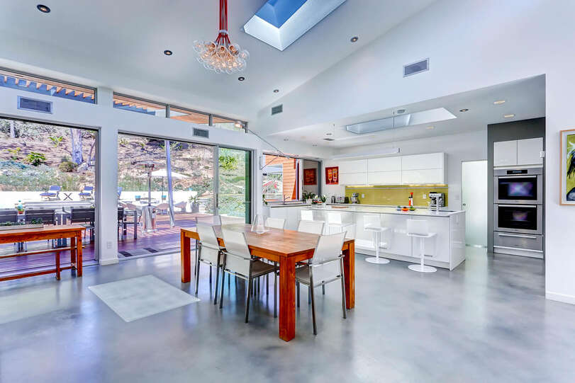 A spacious dining table sits beneath huge skylights and unique fixtures