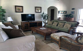 Comfortable and spacious living room with vaulted ceilings and TV