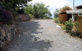 Drive way with natural stone wall and flowering bushes