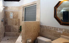 Open designed shower with stone tile and natural light