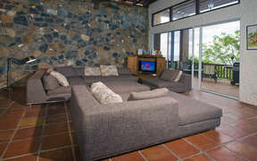 High ceilings and natural stone wall in open air living room with view onto deck