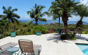 Amazing sunnuy pool deck area with palms, breezes adn View of water