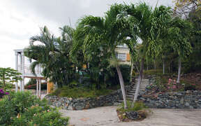 Lush tropical landscaping and native stone walls found throughout the property
