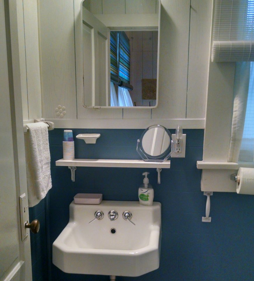 Newly remodeled bathroom.  Original period correct sink, new toilet and new double glass door shower