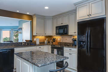 The updated kitchen features granite counters and a center island.